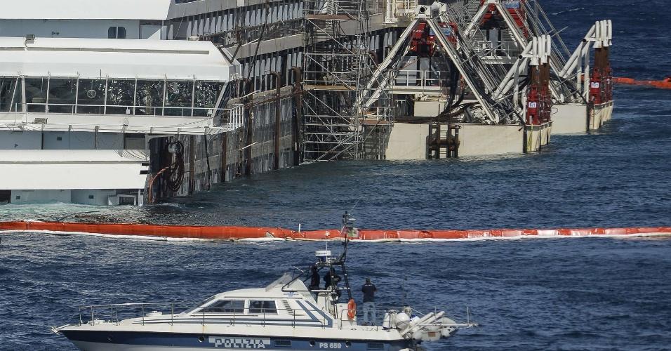 17.set.2013 - Lancha da polícia italiana acompanha a operação que recolocou o navio Costa Concórdia ao nível do mar, nesta terça-feira (17) de manhã, na Ilha de Giglio, na Itália. Os corpos de duas vítimas ainda não foram encontrados pelas equipes de buscas desde que a embarcação adernou, em janeiro de 2012