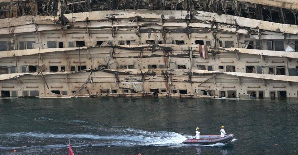 17.set.2013 - Lancha de funcionários de inspeção passa pela lateral do navio Costa Concórdia, nesta terça-feira (17), logo após a conclusão dos trabalhos para nivelar a embarcação, que adernou na ilha de Giglio, na Itália, em janeiro de 2012. Corpos de duas das 32 vítimas ainda não foram encontrados