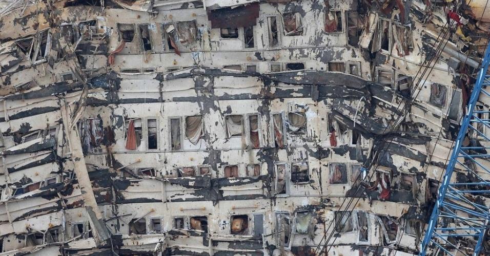 17.set.2013 - Lateral do navio Costa Concórdia que ficou submersa após a embarcação ter adernado, em janeiro de 2012, revela as cabines dos passageiros, com colchões, cortinas e roupas de cama à mostra. Operação que recolocou o navio ao nível do mar foi sem precedentes e considerada um