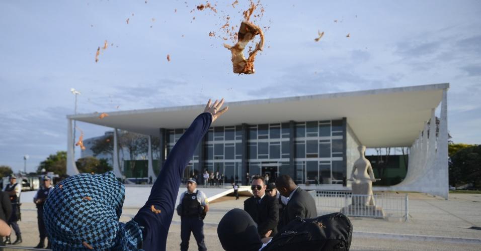 18.set.2013 - Manifestantes atiram pedaços de pizza no prédio do STF (Supremo Tribunal Federal) em protesto contra o voto do ministro Celso de Mello, que desempatou a votação e aceitou os embargos infringentes no julgamento do mensalão, garantindo uma maioria de seis votos pela retomada do julgamento de 12 réus nos crimes de formação de quadrilha e lavagem de dinheiro
