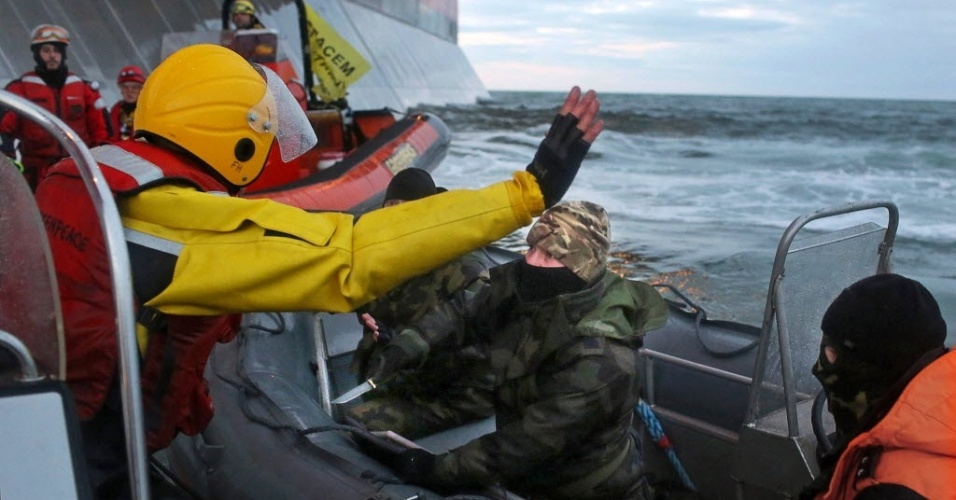 18.set.2013 - Mascarado, homem com trajes da guarda costeira russa aponta uma faca para ativistas do Greenpeace que tentavam invadir a plataforma Prirazlomnaya, da estatal russa Gazprom, no mar de Pechora, no Ártico. Dois militantes foram detidos, mas outros dois conseguiram alcançar a plataforma, se prendendo com cordas ao local