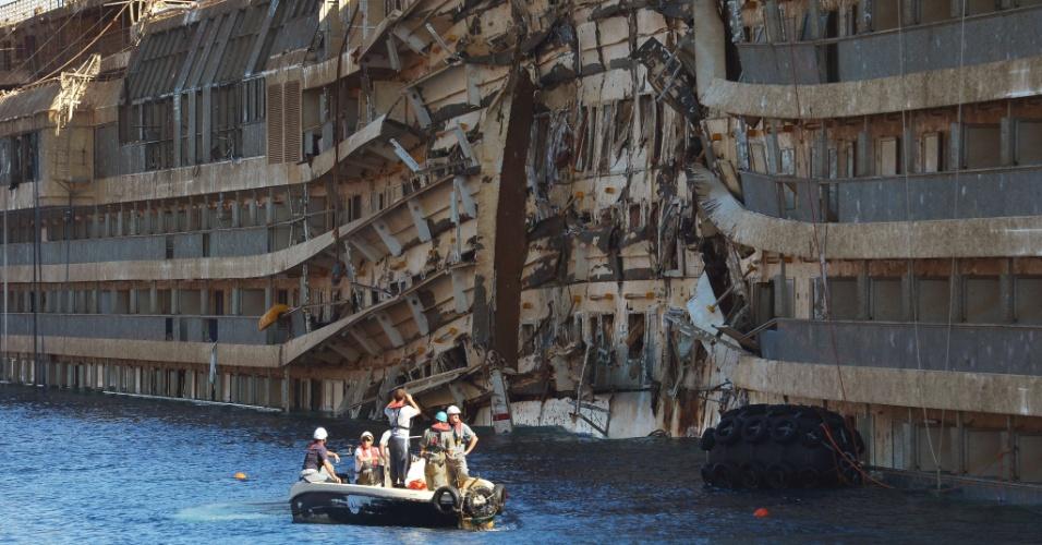 18.set.2013 - Membros das empresas que recolocaram o navio Costa Concordia ao nível do mar inspecionam, nesta quarta-feira (18), o lado da embarcação que ficou submerso desde janeiro de 2012, perto do porto de Giglio, na Itália. Entre os 32 mortos após o acidente, os corpos de duas vítimas ainda não foram encontrados pelas equipes de resgate
