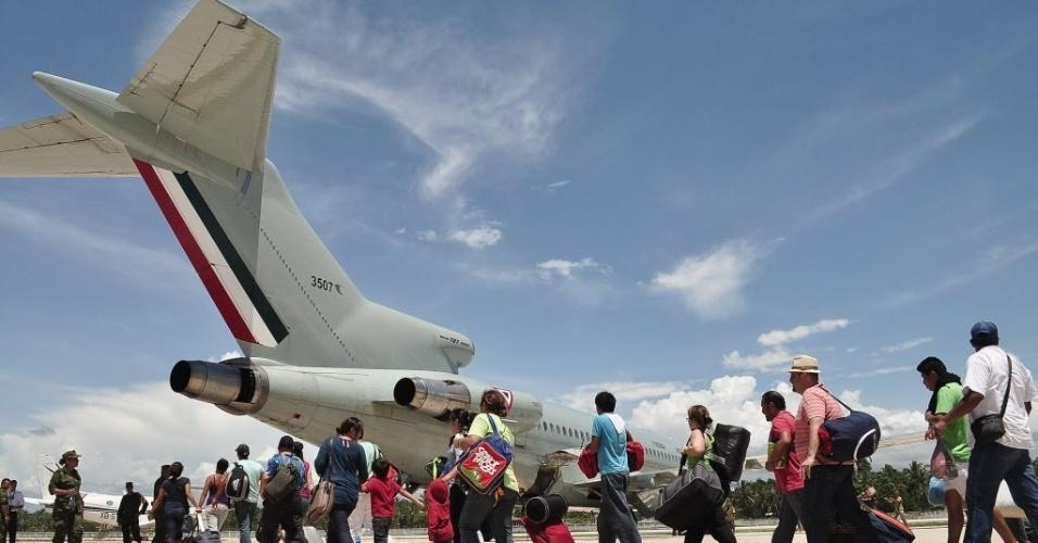 """18.set.2013 - Turistas embarcam em um avião da Força Aérea mexicana, nesta quarta-feira (18) na base militar de Pie de La Cuesta em Acapulco, no Estado de Guerrero. O SMN (Serviço Meteorológico Nacional) informou que a tempestade tropical Humberto, que passou pela região, se transformou em furação perto do litoral do estado mexicano de Sinaloa, com um índice de periculosidade """"forte"""""""