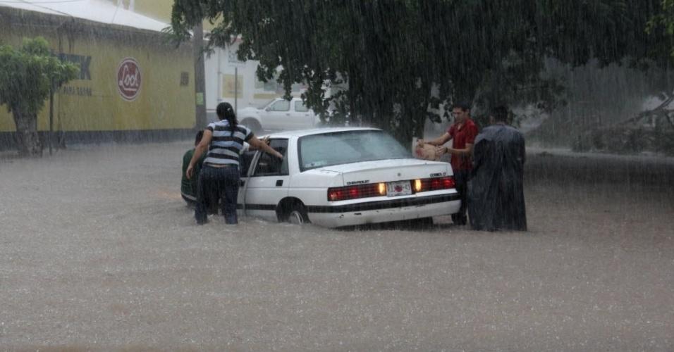 19.set.2013 - Pessoas tentam mover carro de rua inundada em Culiacan, nesta quinta-feira (19). A tempestade tropical Manuel atingiu a costa leste noroeste do México com fortes chuvas