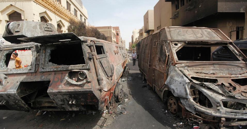 19.set.2013 - Veículos das forças de segurança queimados após confronto com ativistas islâmicos em Kerdasa, uma cidade 14 km do Cairo, nesta quinta-feira (19). O exército tenta tomar o controle da região, dominada por membros da Irmandade Muçulmana, que são contrários ao golpe militar