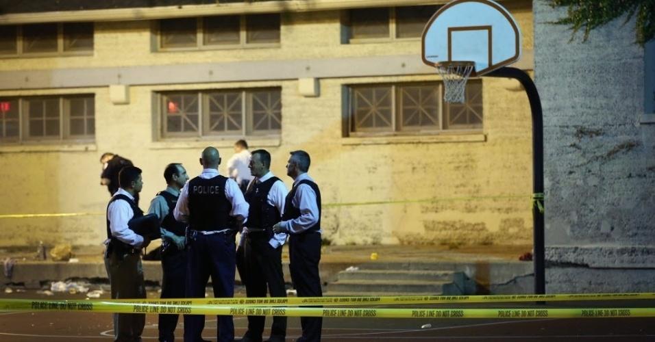 20.set.2013 - Detetives da polícia de Chicago, nos Estados Unidos, se reúnem em quadra de basquete enquanto investigam cena de crime onde ao menos 13 pessoas, incluindo uma criança de três anos, ficaram feridas em um tiroteio em um parque na zona sul da cidade, na noite desta quinta-feira (19). Nenhuma pessoa foi detida por conexão com o tiroteio