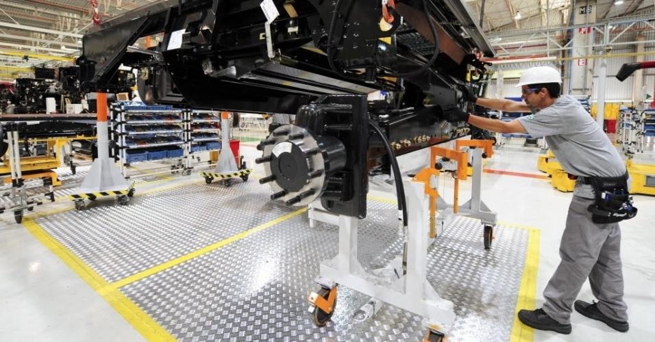 A montagem da máquina é feita em etapas; primeiro grupos menores são montados; na imagem, um operário trabalha no chassi inferior, onde ficam as rodas