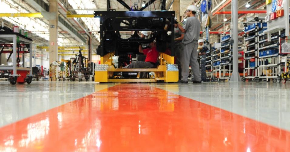 Na linha de montagem, as peças mais pesadas são transportadas por AGVs (Veículos Guiados Automaticamente), como essa máquina amarela ao fundo da foto; eles são programados para seguir essa linha magnética laranja, que pode mudar de lugar e criar uma nova rota, de acordo com as necessidades da fábrica