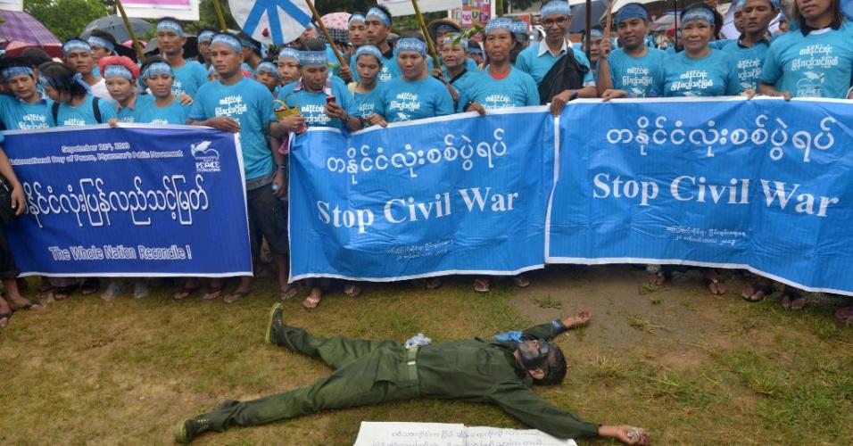 21.set.2013 - Ativista vestido como um soldado deita no chão durante protesto do Dia Internacional da Paz no parque do Povo, em Yangon, no Mianmar, pedindo o fim dos conflitos civis no país