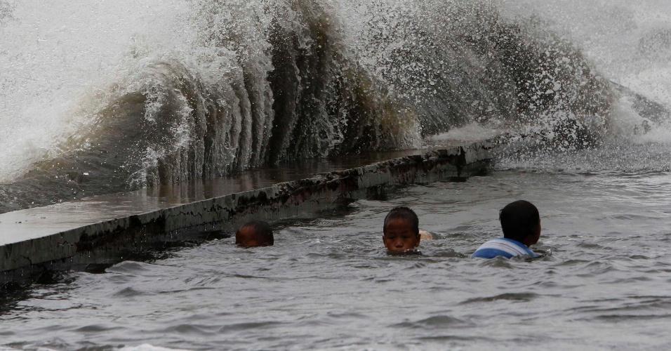 21.set.2013 - Crianças brincam em orla inundada da baía de Manila, nas Filipinas, com ondas fortes trazidas neste sábado (21) pela aproximação do tufão Usagi. Foram registrados ventos de até 220 km/h. Além de inundações, a chegada do tufão causou falhas nas linhas de comunicação e deslizamentos de terra