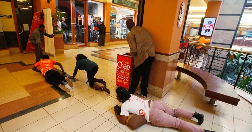 21.set.2013 - Escoltadas por policiais, pessoas rastejam em direção à saída de shopping de Nairobi, no Quênia, onde um tiroteio deixou dezenas de mortos e feridos. Testemunhas afirmaram que os suspeitos atiraram granadas e dispararam contra as pessoas por volta do meia dia, horário em que o prédio estava cheio