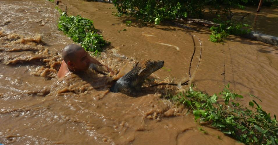 """21.set.2013 - Dono resgata cão que estava sendo arrastado por correnteza em rua inundada durante passagem do furacão """"Manuel"""", em Navolato, no Estado de Sinaloa, no México. Em todo o país, as inundações já deixaram 160 mortos ou desaparecidos, além de 200 mil desabrigados"""