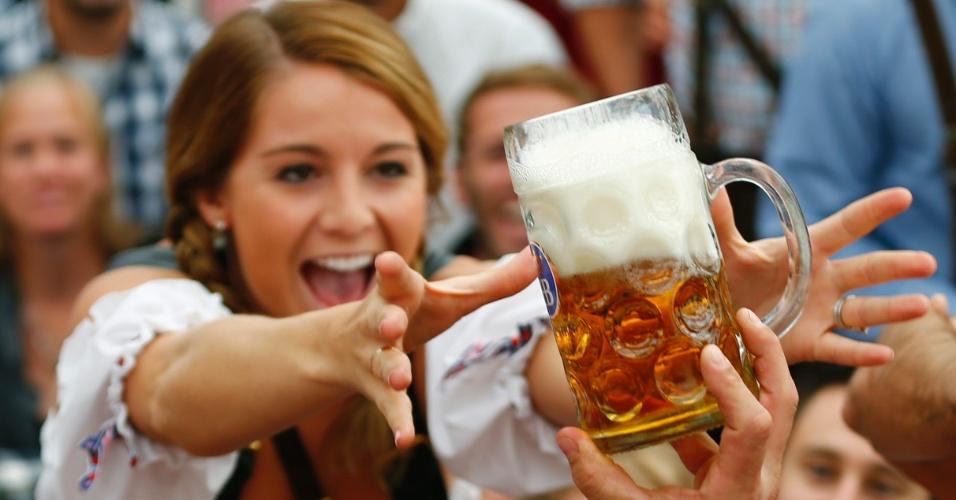 21.set.2013 - Mulher pega uma das primeiras canecas de cerveja distribuídas durante a cerimônia de abertura da 180ª Oktoberfest em Munique, na Alemanha. Milhões de bebedores de cerveja de todo o mundo virão para a capital do Estado alemão da Baviera nas próximas duas semanas para participar do festival, que vai deste sábado (21) a 6 de outubro