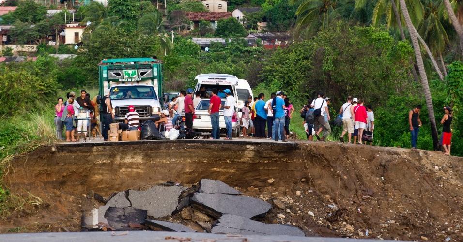 21.set.2013 - Pessoas param em estrada destruída após inundação em Coyuca de Benítez, no Estado de Guerrero, no México. As tempestades no país deixaram 101 mortos e 68 desaparecidos