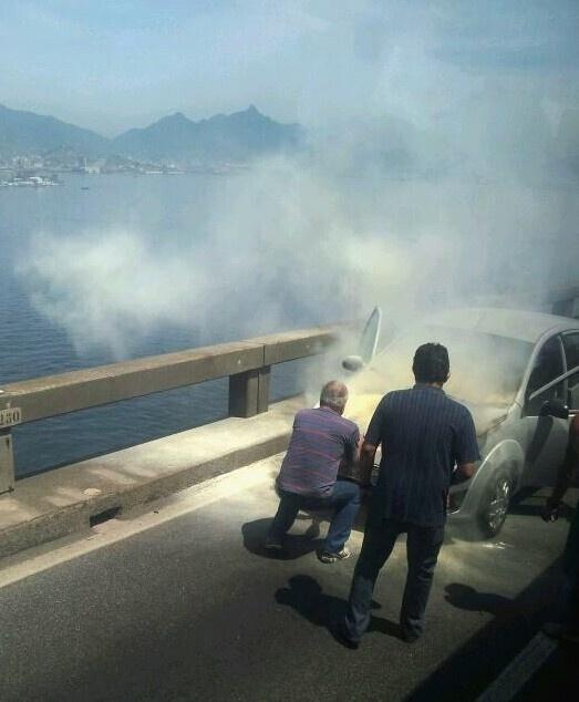 21.set.2013 - Princípio de incêndio em veículo provoca congestionamento na ponte Rio-Niterói, sentido Niterói (RJ), no final da manhã deste sábado (21). Vários motoristas pararam para tentar ajudar o condutor do carro em chamas
