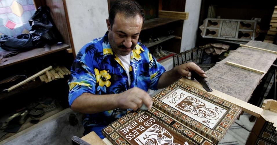 21.set.2013 - Um carpinteiro cristão, membro da Igreja Ortodoxa Síria, dá os retoques finais em uma imagem da Virgem Maria, feita de madeira incrustada com madrepérola, no distrito de Bab Touma, em Damasco