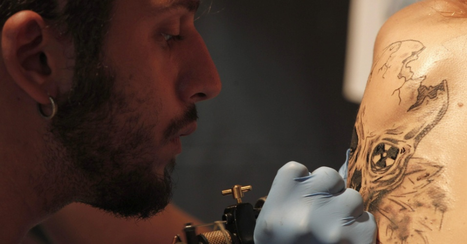 21.set.2013 - Um tatuador trabalha no corpo de um homem durante convenção de tatuagens em  Istambul, na Turquia