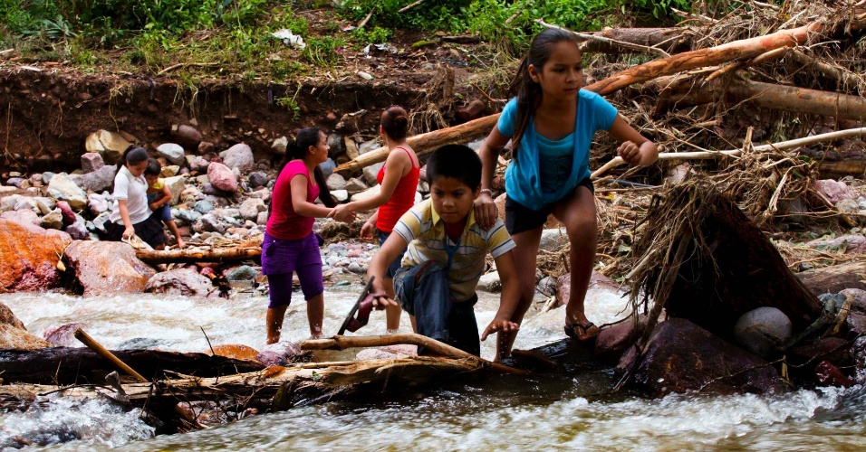 22.set.2013 - Crianças atravessam rio no Estado de Guerrero, no México, após enchentes que causaram mais de uma centena de mortes
