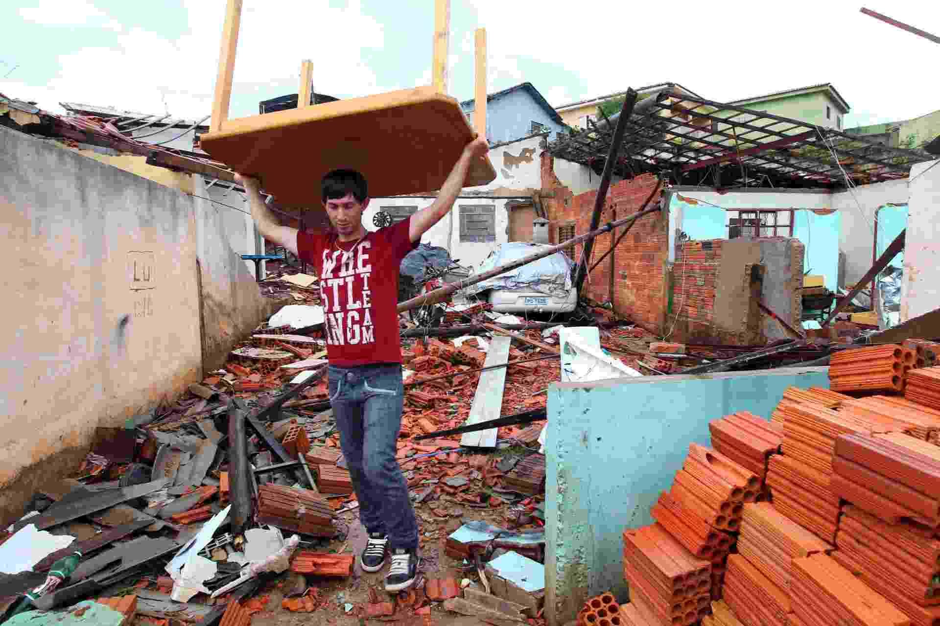 23.set.2013 - Morador carrega mesa em bairro atingido por tornado em Taquarituba, a 320 km de são Paulo, no domingo (22) - Juca Varella/Folhapress