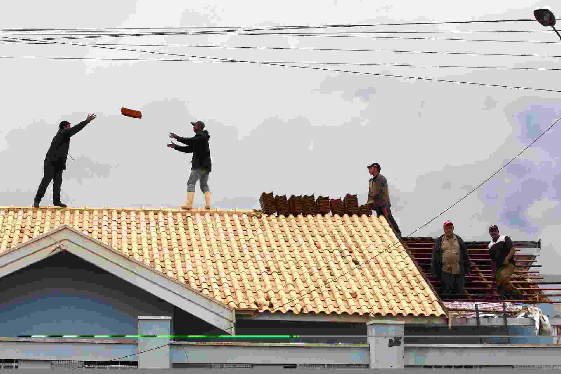 23.set.2013 -  Moradores do bairro BNH, no centro de Taquarituba, fazem mutirão para recolocar telhas levadas pelos fortes ventos do tornado que atingiu a cidade - Juca Varella/Folhapress