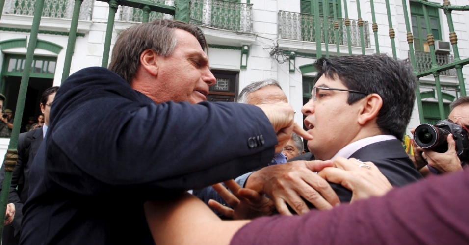 23.set.2013 - O deputado federal Jair Bolsonaro (PP-RJ) (esquerda) e o senador Randolfe Rodrigues (PSOL-AP) discutem enquanto  membros da Comissão da Verdade entravam no 1º Batalhão da Polícia do Exército, na Tijuca, na zona norte do Rio de Janeiro, onde funcionava o antigo DOI-Codi (Destacamento de Operações de Informações - Centro de Operações de Defesa Interna). Bolsonaro, que é radicalmente contrário aos trabalhos da comissão, disse estar no local como forma de protesto. O senador amapaense afirmou que foi agredido por Bolsonaro com um soco na região do estômago