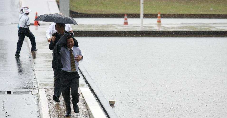 24.set.2013 - Pedestres tentam fugir da chuva próximo à entrada do Congresso Nacional, em Brasília (DF)