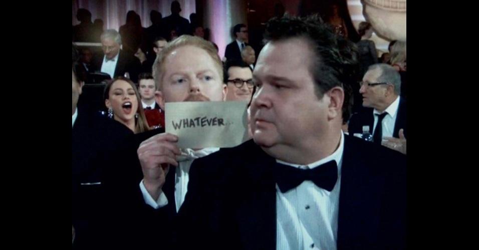 O ator de ''Modern Family'' Jesse Tyler Ferguson mostra cartaz que diz ''E daí...'' atrás do colega Eric Stonestreet, durante a cerimônica do Globo de Ouro de 2012