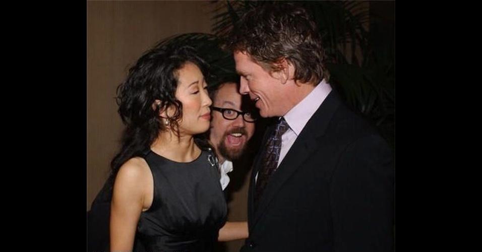 Paul Giamatti estraga a foto da atriz Sandra Oh, de ''Grey's Anatomy''.  As imagens ''photobomb'' (termo em inglês que consiste em algo ou alguém aparecer inesperadamente em uma foto provocando um efeito engraçado) sempre guardam algum elemento engraçado e surpreendente