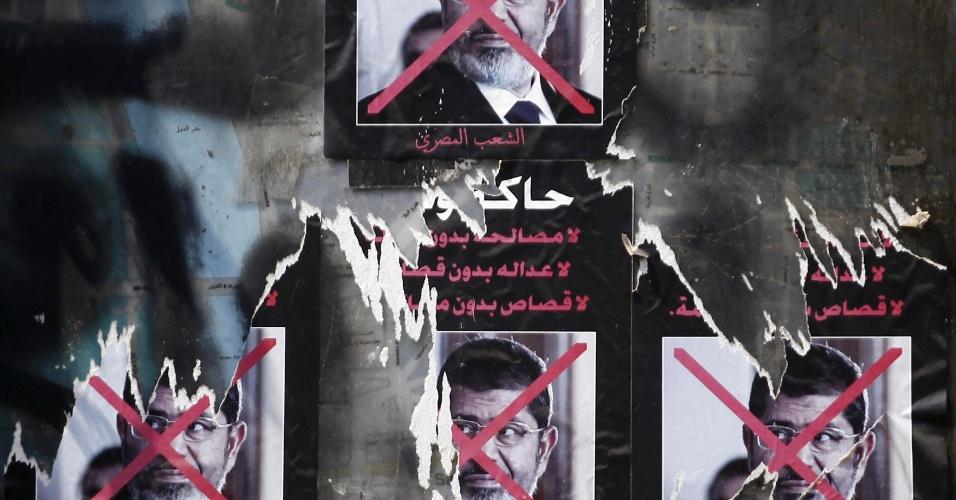 26.set.2013 - Cartazes rasgados do presidente egípcio deposto, Mohamed Mursi, são fotografados em uma parede na praça Tahrir, no Cairo, nesta quinta-feira (26)