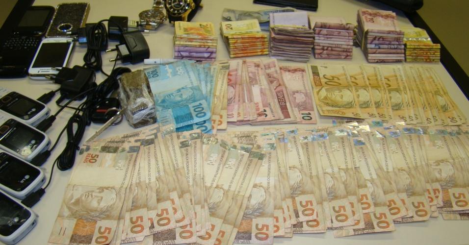 26.set.2013 - Cédulas de dinheiro, em um total superior a R$ 10 mil, são apreendidas por policiais do Batalhão de Polícia Rodoviária em Cabo Frio, no Rio de Janeiro. Também foram apreendidos sete fuzis, maconha, cocaína, ecstasy e crack. Sete pessoas foram presas, entre elas um menor de 16 anos
