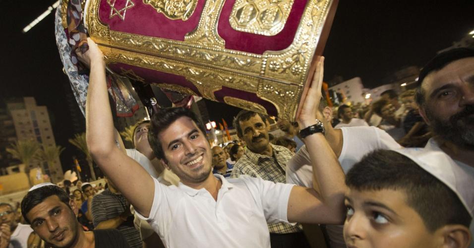 26.set.2013 - Judeus dançam com Torá gigante durante o Simhat Torah, feriado que marca o fim do ciclo anual de leitura da Torá e o início de um novo ciclo, na cidade de Netanya, em Israel