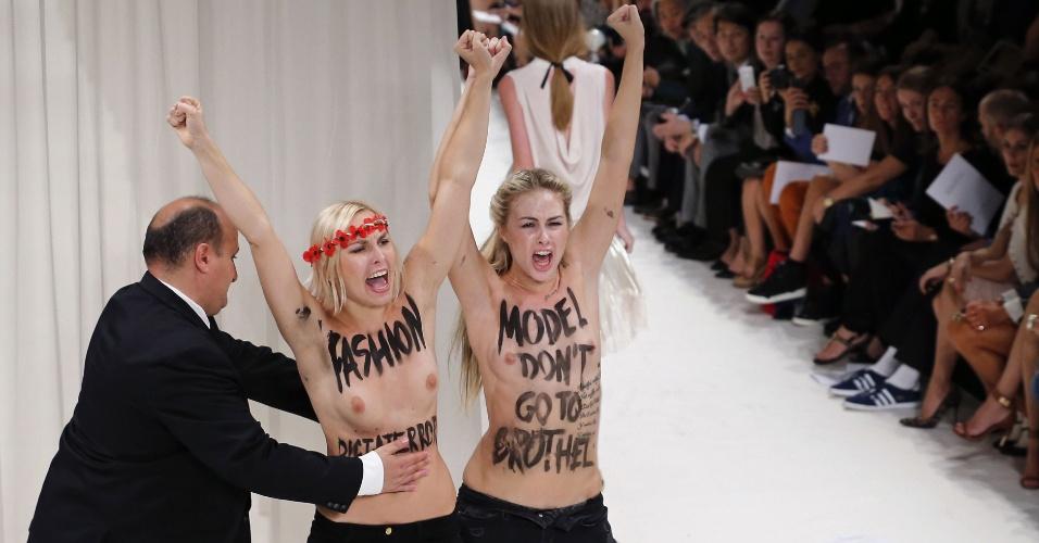 26.set.2013 - Segurança retira ativistas do grupo feminista Femen que invadiram passarela durante desfile Primavera/Verão 2014 da marca Nina Ricci, em Paris, na França