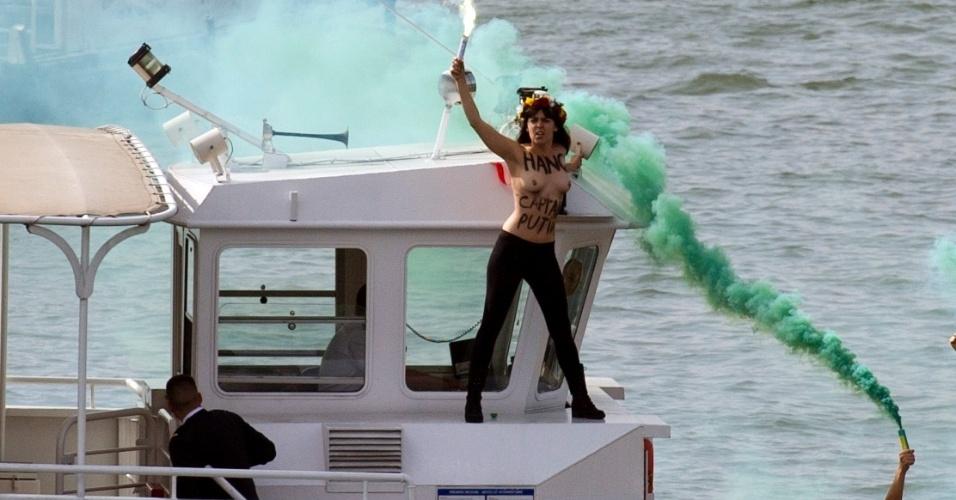 27.set.2013 - Ativista do movimento feminista ucraniano Femen segura sinalizador em um barco que atravessa o rio Sena, na França, durante um protesto em apoio aos 22 membros da tripulação de um navio do Greenpeace que estão presos na Rússia