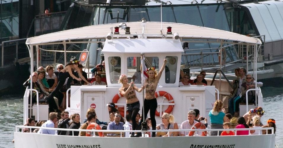 27.set.2013 - Ativistas do movimento feminista ucraniano Femen protestam em um barco que atravessa o rio Sena, na França, em apoio aos 22 membros da tripulação de um navio do Greenpeace que estão presos na Rússia. A Justiça russa decretou nesta sexta-feira (27) a prisão preventiva de 22 dos 30 ambientalistas da organização que foram detidos nas águas do Ártico quando tentavam escalar uma plataforma de petróleo para fazer um protesto