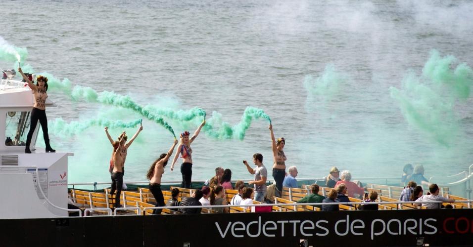 27.set.2013 - Ativistas do movimento feminista ucraniano Femen usam sinalizadores em um barco que atravessa o rio Sena, na França, durante um protesto em apoio aos 22 membros da tripulação de um navio do Greenpeace que estão presos na Rússia. A Justiça russa decretou nesta sexta-feira (27) a prisão preventiva de 22 dos 30 ambientalistas da organização que foram detidos nas águas do Ártico quando tentavam escalar uma plataforma de petróleo para fazer um protesto