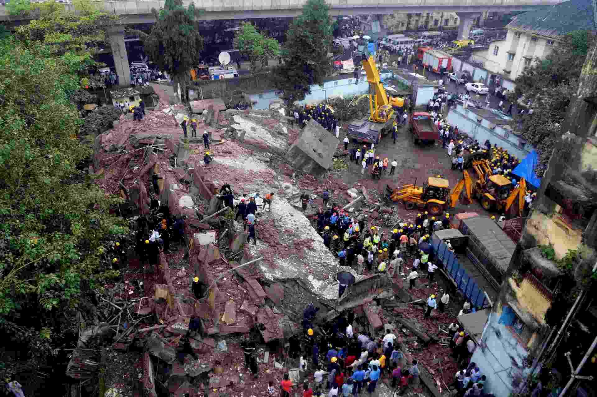 27.set.2013 - Bombeiros procuram sobreviventes nesta quinta-feira (27) em prédio de cinco andares que desabou em Mumbai (Índia). Moradores estimam que cerca de 60 pessoas moravam no local, e a polícia diz que entre 20 e 24 pessoas ficaram presas - Indranil Mukherjee/AFP