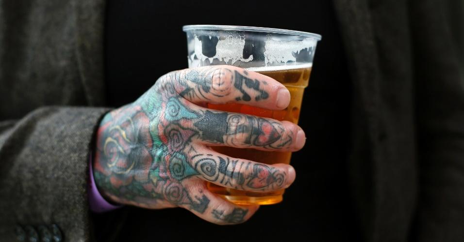 27.set.2013 - Homem tatuado segura um copo com cerveja durante a 9ª Convenção Londrina Internacional de Tatuagem, em Londres, nesta sexta-feira (27)