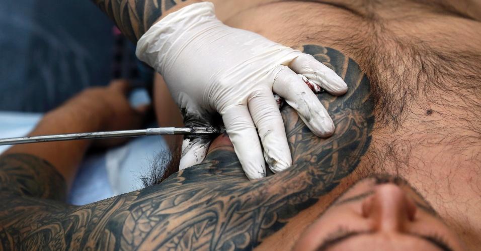 27.set.2013 - O tatuador Chosu Horikazu desenha no peito de homem durante a 9ª Convenção Londrina Internacional de Tatuagem, em Londres, nesta sexta-feira (27)