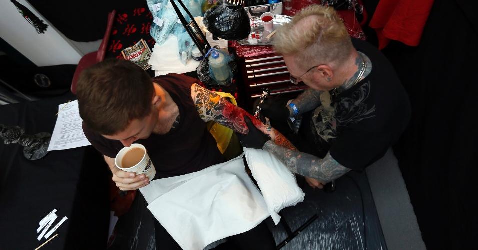27.set.2013 - Um homem toma um café enquanto é tatuado pelo artista George Bone, durante a 9ª Convenção Londrina Internacional de Tatuagem, em Londres, nesta sexta-feira (27)