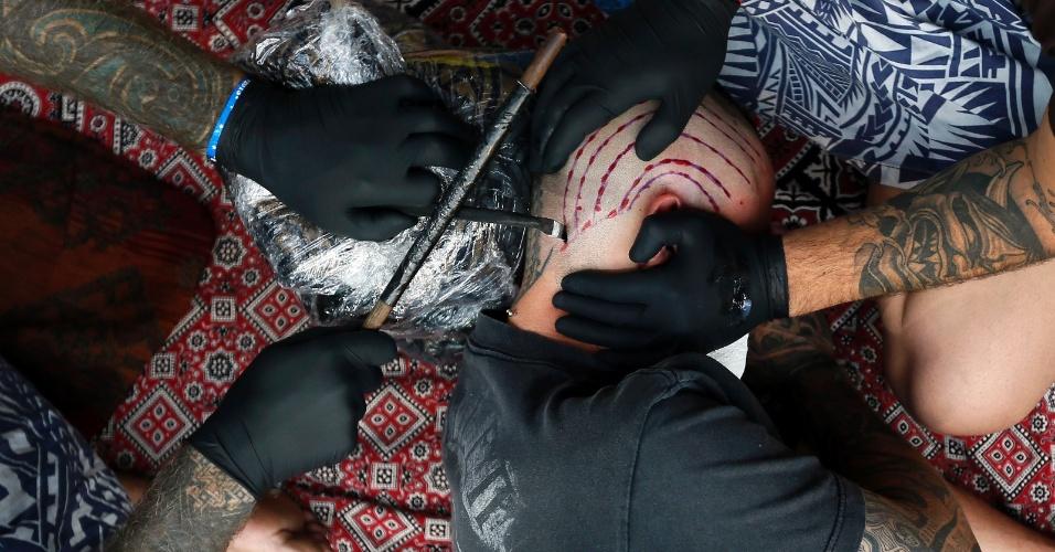 Brent McCown (à esq.) tatua a cabeça de um homem durante a 9ª Convenção Londrina Internacional de Tatuagem, em Londres, nesta sexta-feira (27)