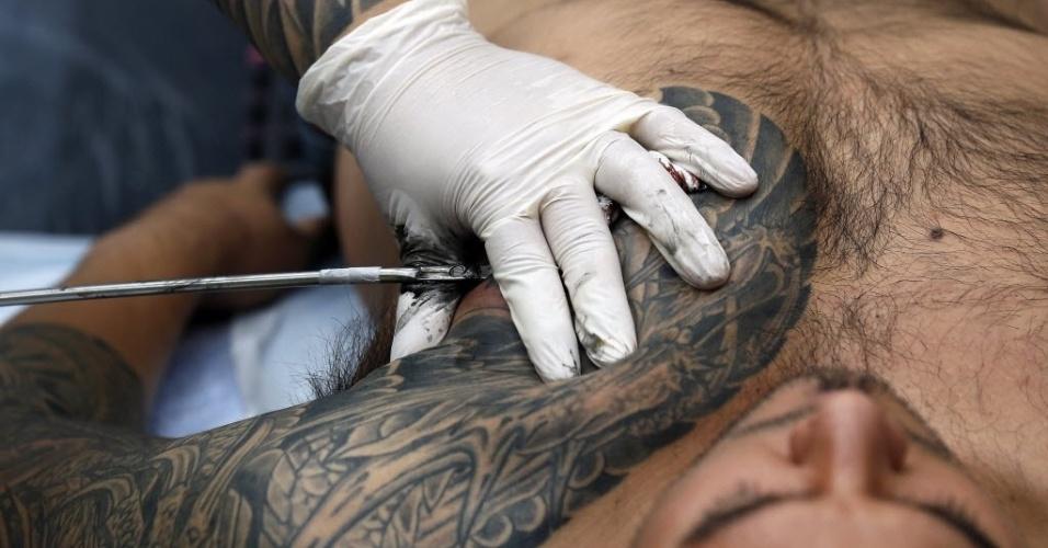 28.set.2013 - Jovem é tatuado pelo artista Chosu Horikazu (à esquerda) durante 9ª Convenção Internacional de Tatuagem em Londres. O evento reúne cerca de 300 artistas