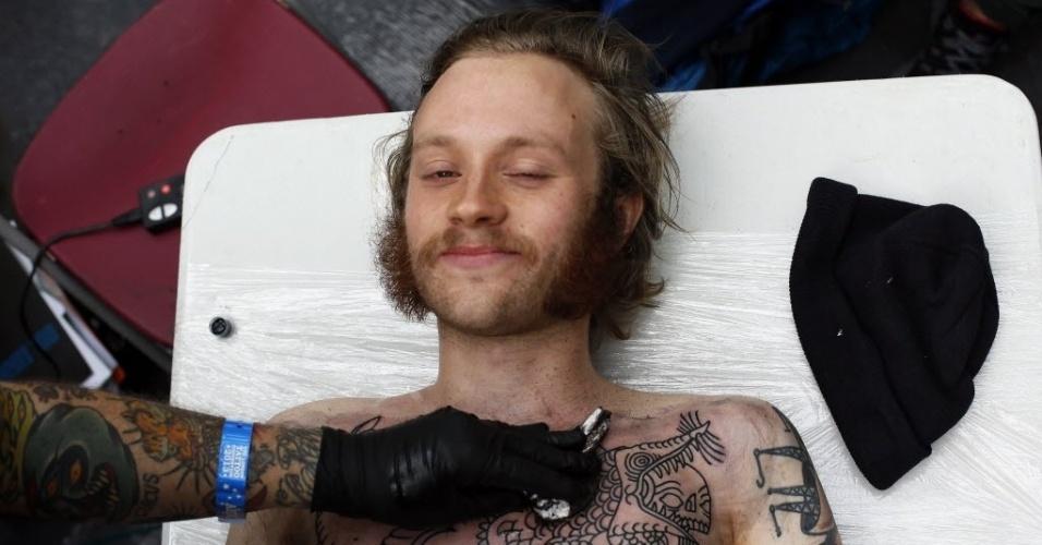 28.set.2013 - Jovem é tatuado pelo artista Deno (à esquerda) durante 9ª Convenção Internacional de Tatuagem em Londres. O evento reúne cerca de 300 artistas