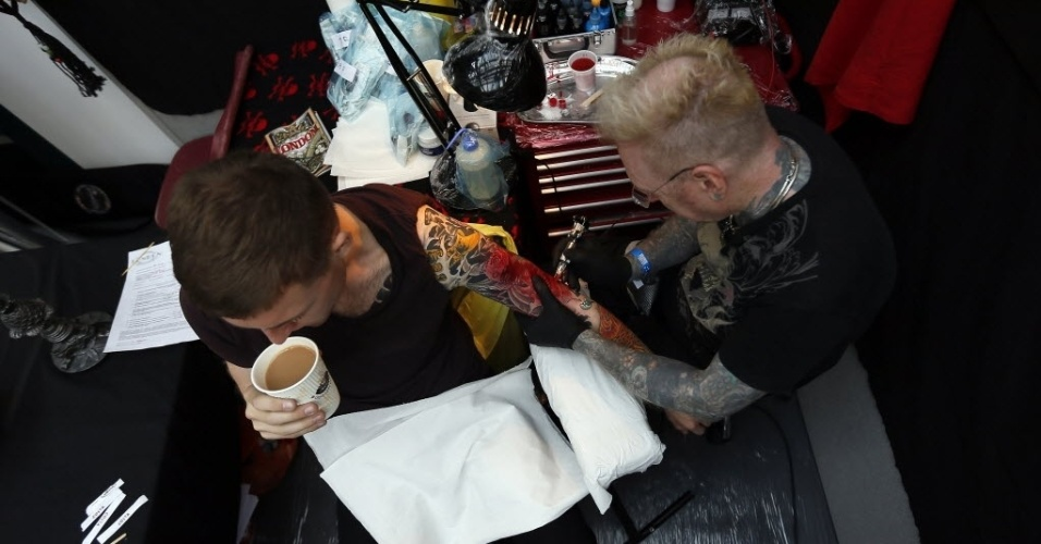 28.set.2013 - Jovem é tatuado pelo artista George Bone (à direita) durante 9ª Convenção Internacional de Tatuagem em Londres. O evento reúne cerca de 300 artistas