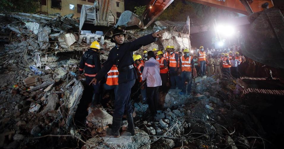 28.set.2013 - Socorrista pede maca para resgatar sobreviventes durante trabalho de buscas por entre destroços de prédio de cinco andares que desabou em Mumbai (Índia)