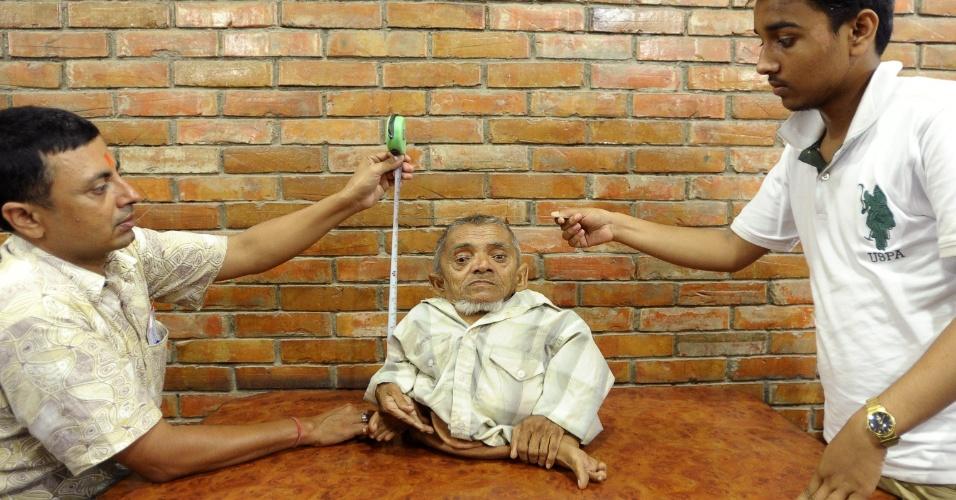 30.set.2013 - Master Nau, nepalês de 73 anos e 40,6 cm de altura, é medido em cima de uma mesa, em Kathmandu, para desafiar o atual recordista de menor homem do mundo do Guinness - O Livro dos Recordes. Se confirmado, ele pode ser oficializado como menor que o seu rival, um taiwanês de 68,5 cm. Nau vive com a família de seu irmão mais novo em Bhairahawa, a 350 quilômetros (217 milhas) a sudoeste de Katmandu, no Nepal