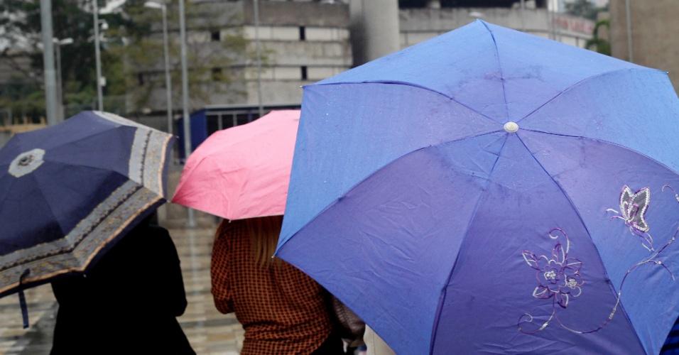 30.set.2013 - Pedestres caminham com guarda-chuvas pelo terminal de ônibus de Pinheiros, na zona oeste de São Paulo, nesta segunda-feira (30). A capital paulista chegou a registrar cinco pontos de alagamento após as chuvas