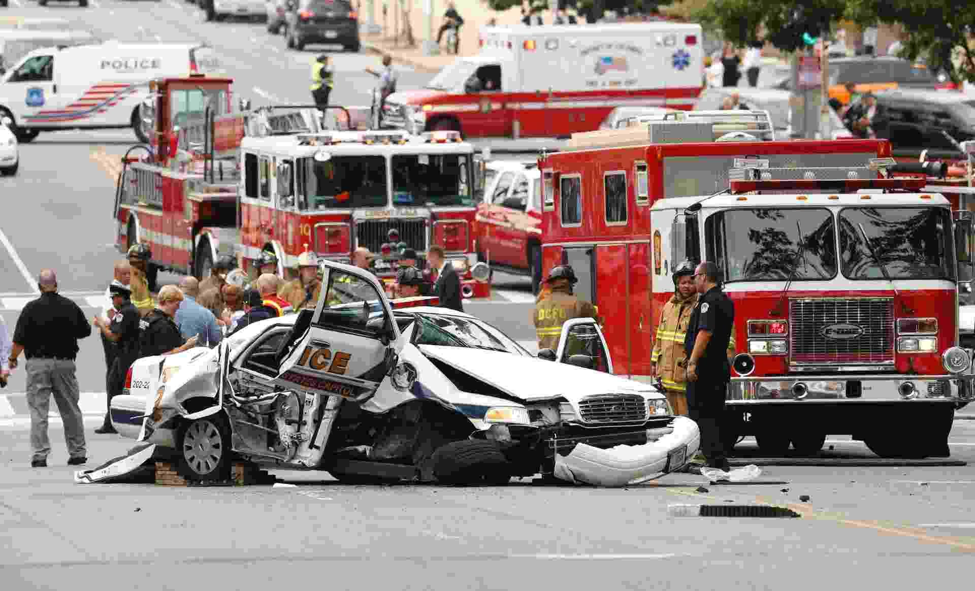 3.out.2013 - Equipes de resgate se posicionam ao redor de um carro de polícia que sofreu uma batida, próximo ao Capitólio, nesta quinta-feira (3). Disparos de arma de fogo foram ouvidos do lado de fora do prédio onde funciona o Congresso norte-americano - Kevin Lamarque/Reuters