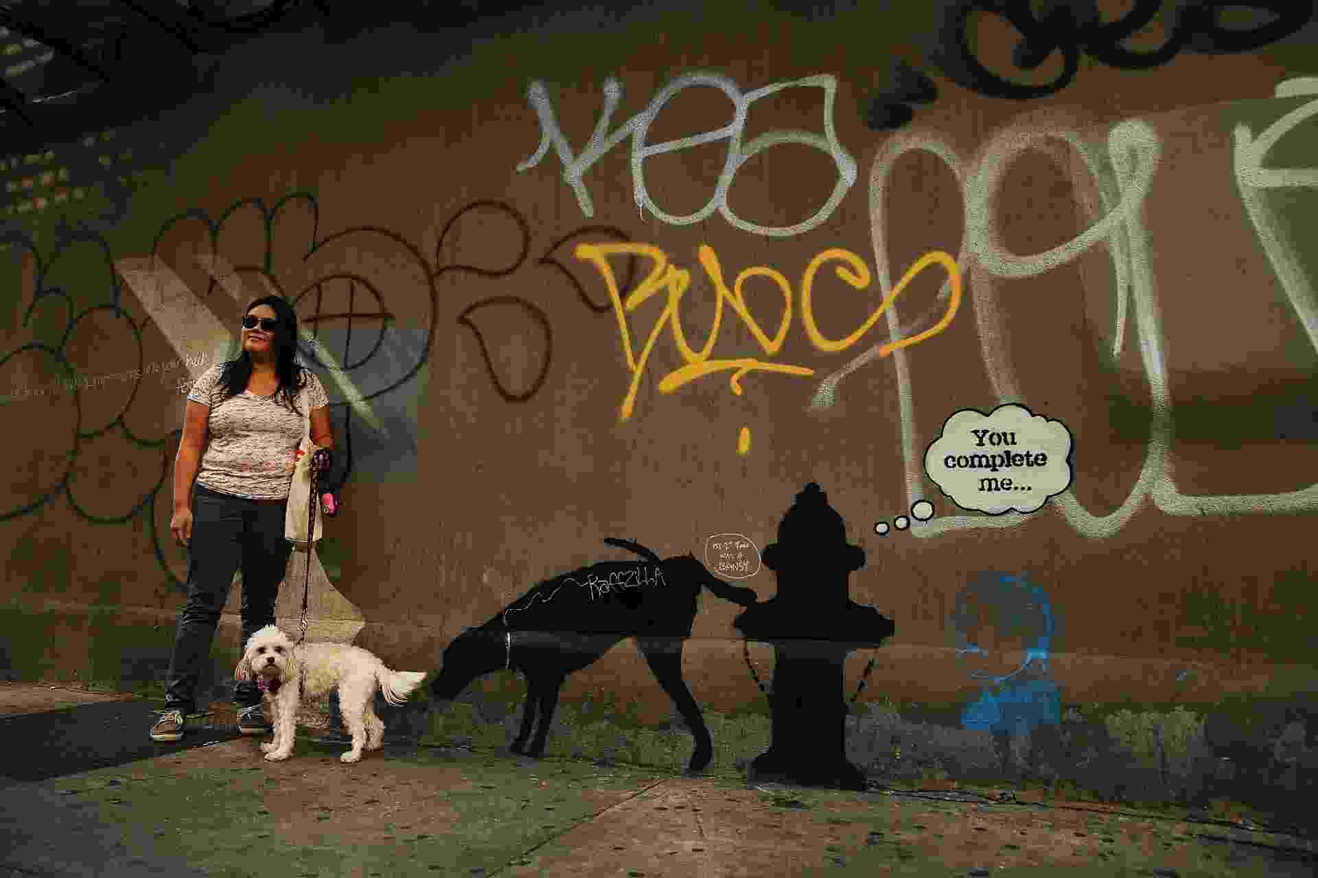 3.out.2013 - Mulher posa com seu cachorro ao lado de um grafite atribuído ao artista britânico Banksy, nesta quinta-feira (3), em Nova York. A identidade do pintor - que anunciou uma temporada de três meses na cidade - é desconhecida - Spencer Platt/AFP