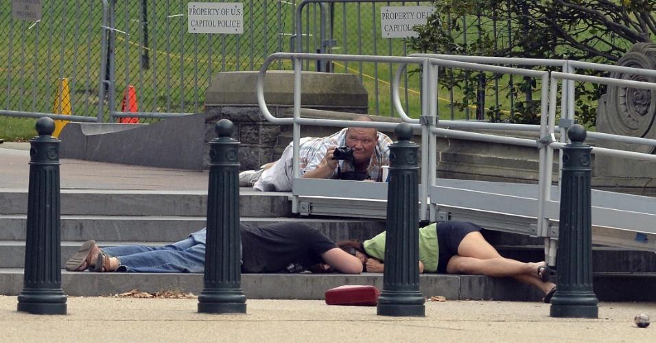 3.out.2013 - Pessoas se deitam no chão tentando se proteger de disparos de arma de fogo nesta quinta-feira (3), nos arredores do Capitólio, em Washington. O local foi colocado em bloqueio de segurança, após tiros terem sido ouvidos do lado de fora do prédio onde funciona o Congresso norte-americano