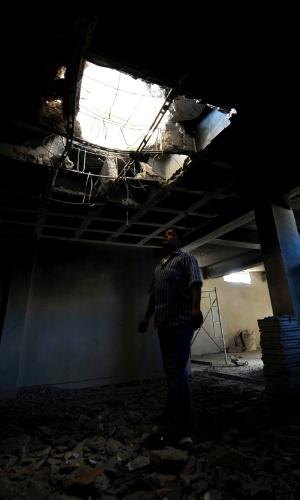4.out.2013 - Policial observa estação de polícia danificada pela explosão de uma bomba, em Benghazi (Líbia), nesta sexta-feira (4). Dois policiais ficaram feridos e um morreu